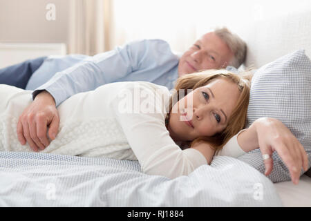 Portrait of mature couple relaxing on bed at home