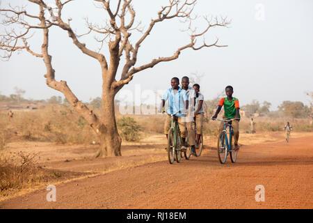 Yako Province, Burkina Faso; Boys on their way to school on the road from Yako town to Samba. - Stock Photo