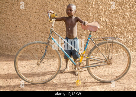 Samba village, Yako Province, Burkina Faso: A young boy with an adult bike. - Stock Photo