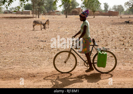 Samba village, Yako Province, Burkina Faso: A teenage girl transports two canisters of water from the well to her home on her bike. - Stock Photo