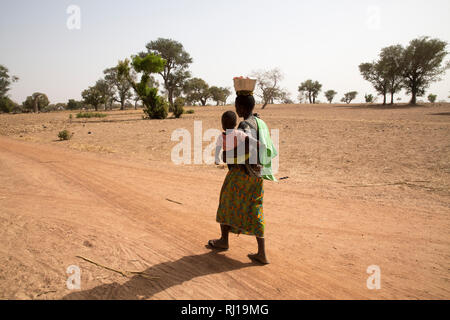 Samba village, Yako Province, Burkina Faso; Sally Zoundi, 35, with her baby Salomon Zoundi, 15 months, on her way to work at the local goldmine to support her family. - Stock Photo