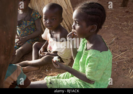 Samba village, Yako Province, Burkina Faso : Children eating fruit. - Stock Photo