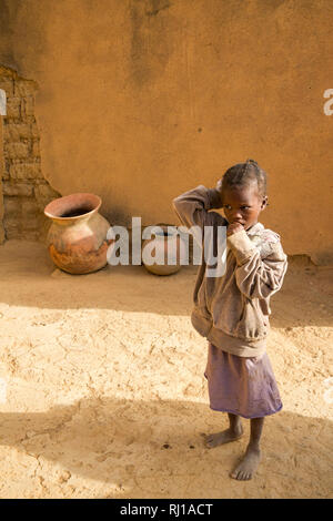 Samba village, Yako Province, Burkina Faso : a young girl, watches while her mother talking to other villagers. - Stock Photo