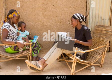 Baribsi village, Yako province, Burkina Faso; Sally Belem, 32,  conducting a survey into child nutrition interviews a teenage mother. - Stock Photo