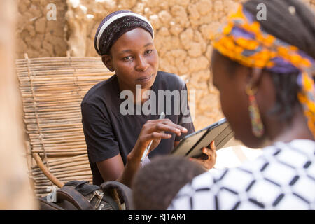 Baribsi village, Yako province, Burkina Faso; Sally Belem, 32,  conducting a survey into child nutrition interviews a teenage mother. - Stock Photo