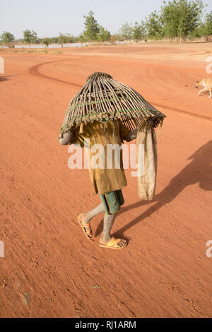 Samba village, Yako Province, Burkina Faso: A young boy carryng a fishing basket to catch fish in the lake on one of the days when fishing is allowed. - Stock Photo