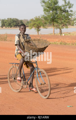 Samba village, Yako Province, Burkina Faso: A young fisherman on his way with his fishing baket to catch fish in the lake on one of the days when fishing is allowed. - Stock Photo
