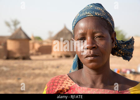 Kourono village, Yako province, Burkina Faso; A portrait of a woman with tribal marking on her face, in front of village grain stores. - Stock Photo