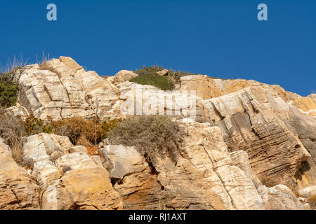 Natural texture of rocks against blue sky. Cracked and weathered natural stone background - Stock Photo