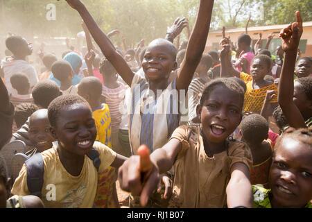 Samba village, Yako Province, Burkina Faso: Children celebrate after their school wins an inter-school football match. - Stock Photo