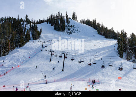 Skiing at Squaw Valley resort in Placer County, California. People on a chair lift, downhill skiing and skiing a mogul run. - Stock Photo