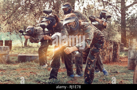 Expressive paintball team running with marker guns at an open playing field - Stock Photo