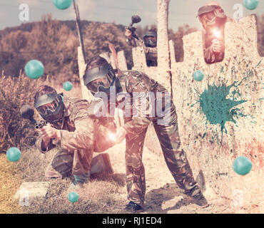 Expressive paintball team running with a marker guns at an open playing field - Stock Photo
