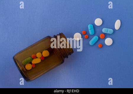 Colored pills on a light blue background next to a glass bottle containing drugs. Drugs for use in humans. - Stock Photo