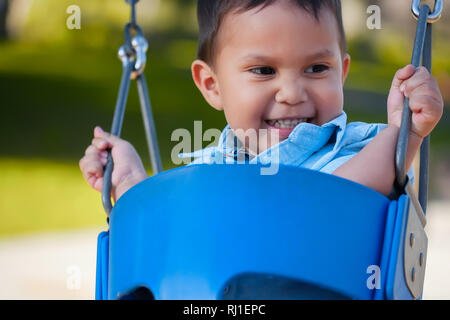 Young hispanic boy with a cute smile that is looking away while riding and holding on to a playground swing. - Stock Photo