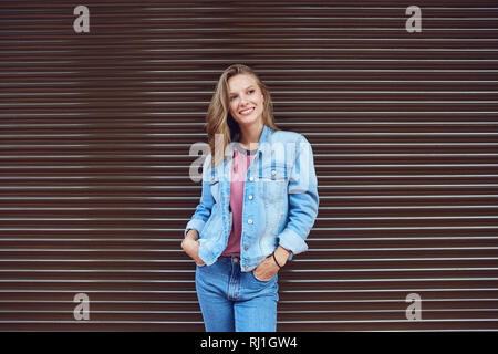 Blonde girl smiling on a striped  background .. - Stock Photo