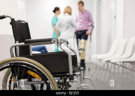 Closeup of wheelchair against patient and doctors at hospital - Stock Photo