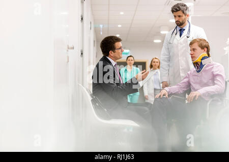 Specialist talking to disabled man while doctors walking in hospital corridor - Stock Photo