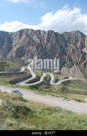 A car winds its way over the switchbacks of a high mountain pass in Kyrgyzstan - Stock Photo