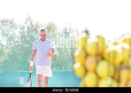 Mature man playing tennis against clear sky on sunny day - Stock Photo