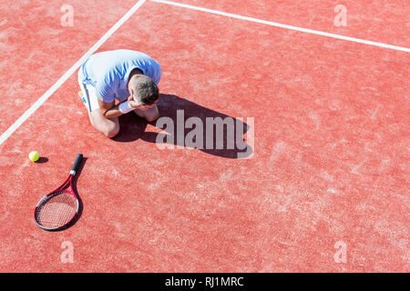 High angle view of disappointed mature man with head in hands while kneeling by tennis racket on red court during summer - Stock Photo