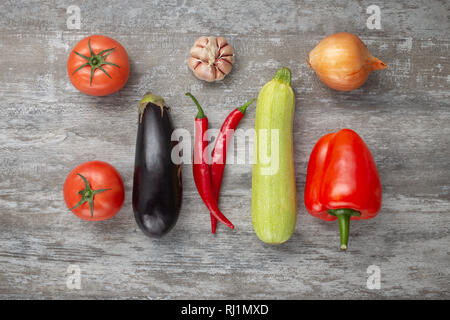 fresh vegetables on wooden background, tomatoes, eggplant, zucchini, pepper, garlic, onion, top view - Stock Photo