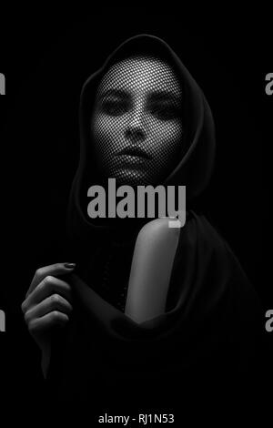 serious female beautiful face with stocking on head looking at camera on black background monochrome - Stock Photo
