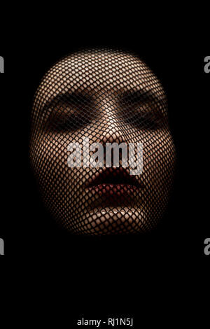 serious female beautiful face with stocking on head, black background, closed eyes - Stock Photo