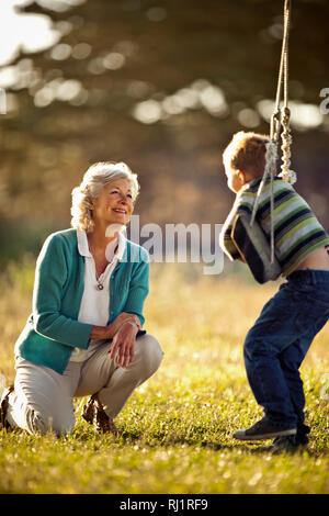 Little boy playing on the tree swing with his grandmother. - Stock Photo