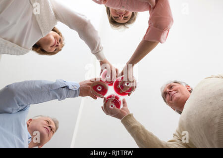 Directly below view of mature friends toasting wineglasses at home - Stock Photo