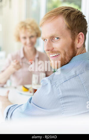 Portrait of smiling man sitting with woman in restaurant - Stock Photo