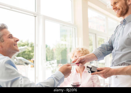 Smiling mature man paying through credit card at restaurant - Stock Photo
