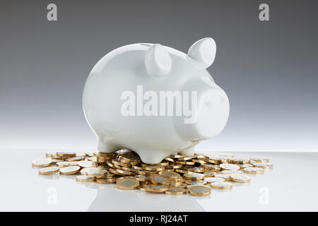 White Contemporary Piggy Bank with Pound Coins - Stock Photo