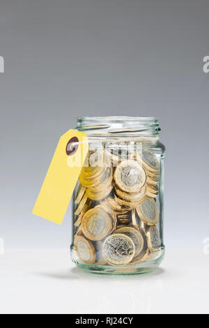Glass Savings Jar with One Pound Coins - Stock Photo