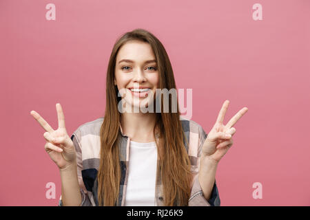 Young caucasian woman over isolated background smiling looking to the camera showing fingers doing victory sign. Number two - Stock Photo