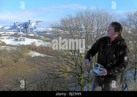 A man flying a drone in a rural winter snowy landscape in the countryside of Carmarthenshire Wales UK  KATHY DEWITT - Stock Photo
