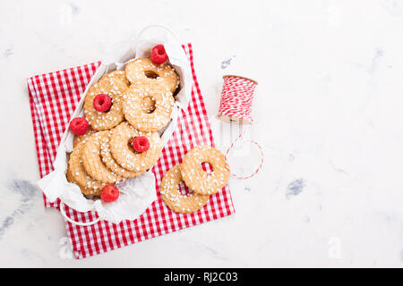 Cookies with sugar drops in a metal bowl with raspberries ready to decorate for holiday or gift, top view with place for text - Stock Photo