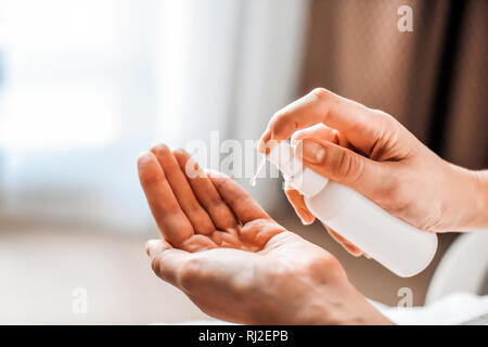 A woman puts on the hands of cosmetics from a bottle or liquid natural soap. Body care concept - Stock Photo