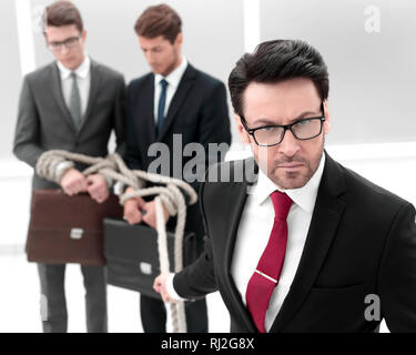 close up. serious businessman pulls business partners tied with a rope - Stock Photo
