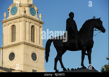 Equestrian statue of King George IV and Baroque St Martin In The Fields Church built 1721 to 1726 designed by James Gibb on Trafalgar Square in London - Stock Photo