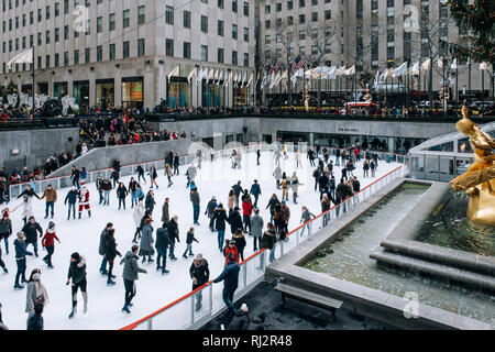 New York City - USA - DEC 17 2018: Seasonal ice skating rink with a golden statue, in a famed complex with upscale shops & restaurants in Rockefeller  - Stock Photo