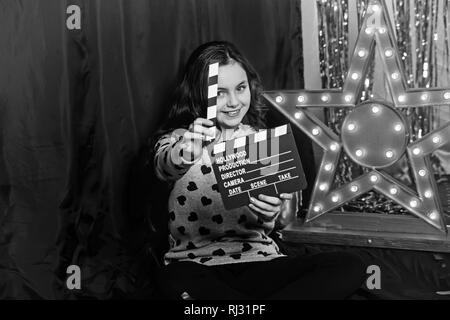 Happy child play with movie clapper or clapperboard. Little girl smile in film studio at golden star with light bulbs. Movie and film production - Stock Photo