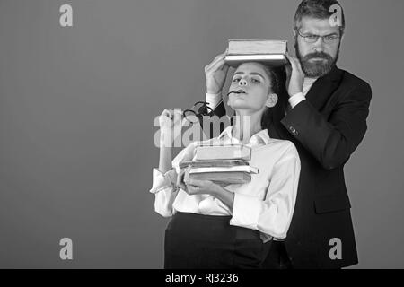 Education in knowledge day. Literature lesson and reading grammar book. Teacher man and girl hold book pile on head. Back to school and home schooling - Stock Photo