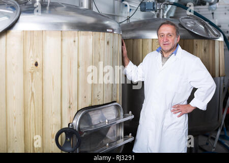 Adult brewer is standing near barrel for beer in the fabric. - Stock Photo