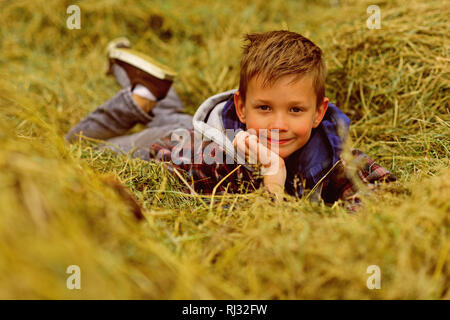 Small dreamer. Small boy relax in haystack. Small boy daydreaming in haystack hill. Looking for a needle in a haystack - Stock Photo