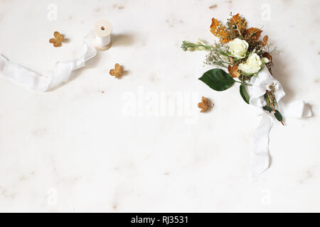 Feminine winter wedding, birthday still life scene. Silk ribbon and bouquet of dry maple leaves, hydrangea, white roses and gypsophila flowers, marble - Stock Photo