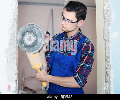 Young man worker using professional angle grinder for cutting wall - Stock Photo