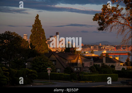 Seattle Skyline from Magnolia Bluff sunset with homes and tanker in Elliott Bay - Stock Photo