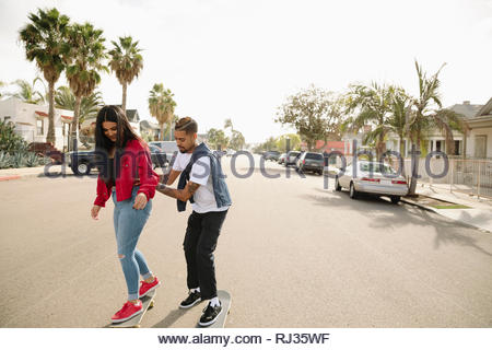 Latinx man teaching girlfriend how to skateboard on sunny neighborhood street - Stock Photo