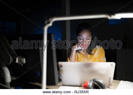 Dedicated businesswoman working at laptop in dark office - Stock Photo